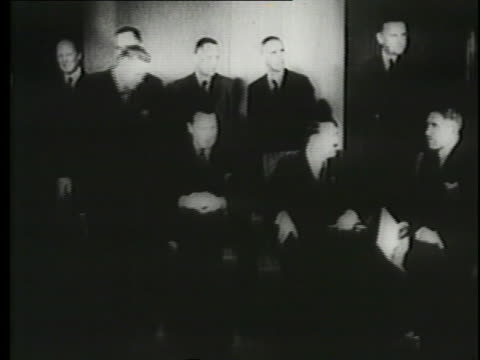 a montage shows a newspaper clip and a meeting of officials with adolf hitler. - newspaper clipping stock videos and b-roll footage