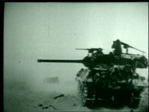 a montage shows artillery firing into a field, tanks rolling over the snow, general patton, and marching soldiers. - ardennenoffensive stock-videos und b-roll-filmmaterial