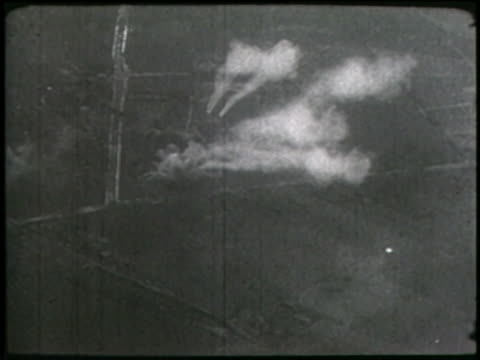 a montage shows bombs dropping on a countryside and a war zone at night. - world war ii stock videos & royalty-free footage