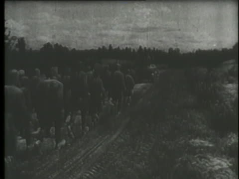 a montage shows prisoners of war walking through snow and proceedings at the nuremberg trials. - prisoner of war stock videos & royalty-free footage
