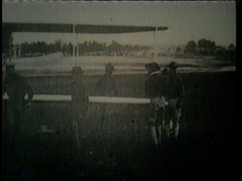vídeos de stock, filmes e b-roll de a montage shows the wright brothers' plane the kitty hawk in its first flight. - wilbur wright