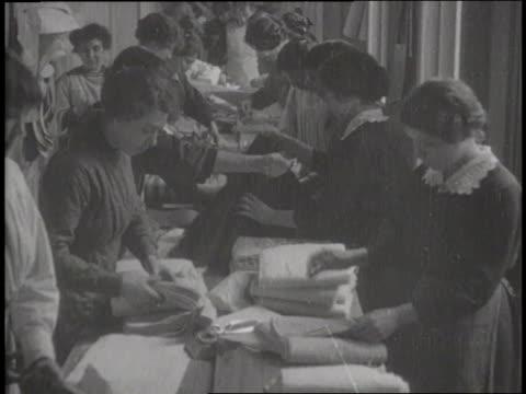 vidéos et rushes de montage shows women doing various factory jobs like folding fabric, putting labels on bottles and sealing liquor bottles. - 1910