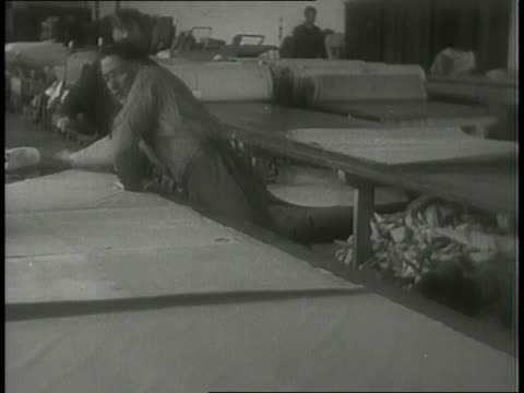a montage shows workmen stretching and cutting fabric, stretching it over a frame, and the finished shell. - cutting stock videos & royalty-free footage