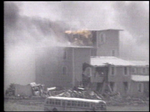 Montage siege at Branch Davidian cult compound ATF agent on roof firing his gun and being shot wounded being carried away compound burning Montage...