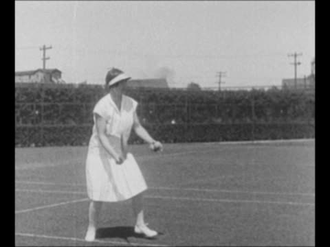 stockvideo's en b-roll-footage met montage slo-mo tennis player helen wills moody returns a lob, serves tennis ball in match / from greatest headlines of the century series - atlete
