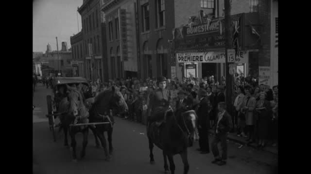 montage south dakota city includes panorama and aerial views / ls spectators in period costume line streets as parade for film premiere of 'calamity... - wild west stock videos & royalty-free footage