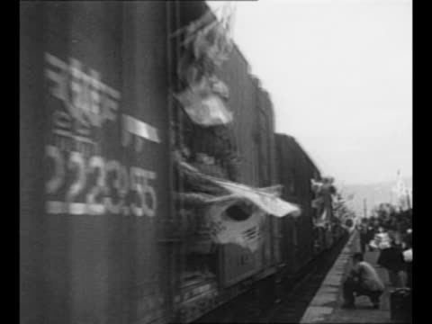 stockvideo's en b-roll-footage met montage south korean soldiers walk many waving small south korean flags after end of korean war / train approaches with south korean soldiers waving... - koreaanse oorlog