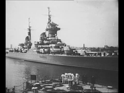 montage soviet cruiser ordzhonikidze pulls into harbor approaches pier / line of soviet navy sailors stand at rail of ship with gun turret in... - 1956 stock videos and b-roll footage