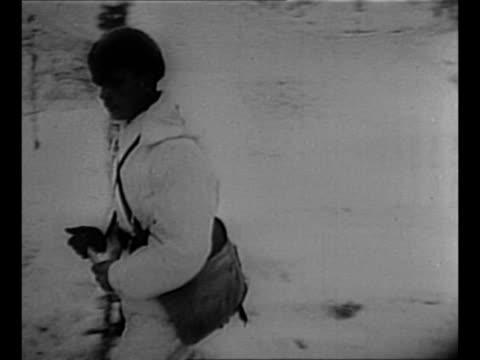 Montage Soviet POWs wearing dark uniforms stand on snowy ground in compound in Finland during Winter War / whiteclad Finnish soldier enters dugout in...