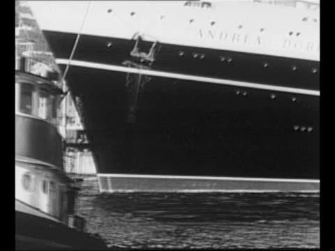 Montage SS Andrea Doria in port in Italy / bow of ship with label Andrea Doria smaller boat passes by in foreground / smokestack with smoke / Andrea...