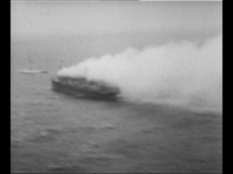 vídeos de stock e filmes b-roll de montage ss morro castle burns as it sails in rough waters in the atlantic ocean; burned areas and some people on deck can be seen; lifeboat hangs... - embarcação comercial