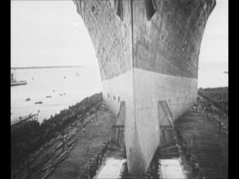 montage ss normandie slides toward water during launch in 1932 / men stand on stern as ship moves away from dock / ship slides into water / ws... - normandie stock-videos und b-roll-filmmaterial