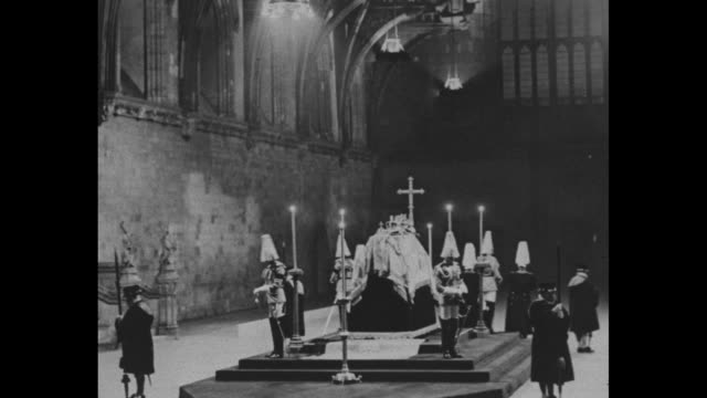 stockvideo's en b-roll-footage met montage still king george v lies in state at westminster hall in london's palace of westminster with coffin on platform surrounded by candles and... - opgebaard liggen