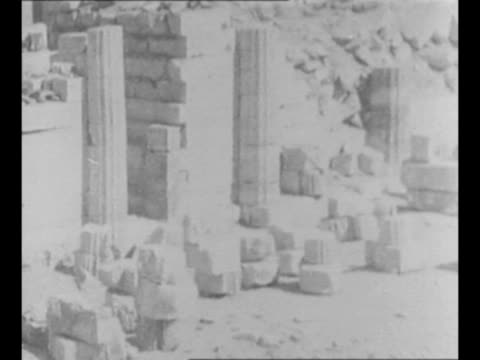 vídeos y material grabado en eventos de stock de montage stone columns and monuments unearthed from earlier archaeological dig probably in saqqara / montage workers and carts at excavation site /... - excavar