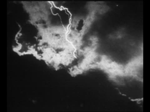 Montage storm clouds lightning in sky / clothes on clothesline sway in wind as rain falls on them hand starts to unclip them from line / sheep in pen...
