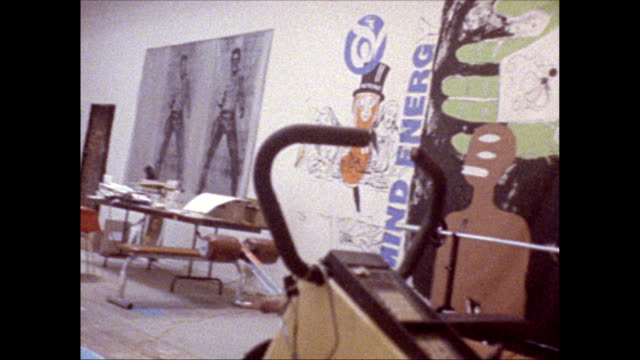 / montage studio men working on silkscreens on the floor painting hanging on the wall including double Elvis JeanMichel Basquiat work
