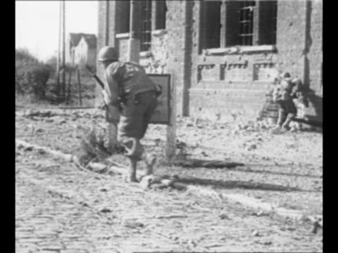 montage tanks fire as allied forces enter aachen germany during world war ii / smoke in city street / allied soldiers cautiously pass road sign... - ノルトラインヴェストファーレン州点の映像素材/bロール