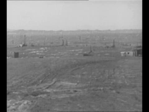 montage teapot dome oil field and derrick in wy / oil shoots up inside derrick / ms us secretary of the interior albert bacon fall / from greatest... - 1920~1929年点の映像素材/bロール