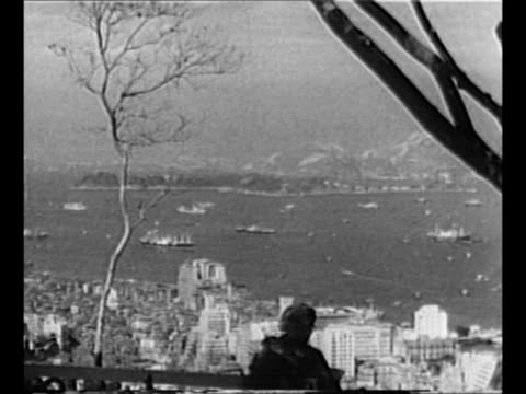 Montage WS Tokyo and harbor with ships with person sitting in foreground at beginning / military airplane sits on tarmac with jellied gasoline...