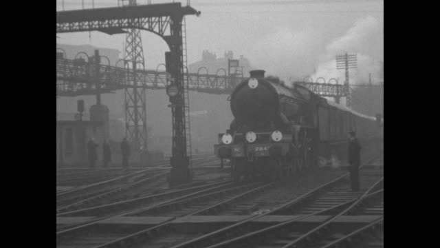 stockvideo's en b-roll-footage met montage train bearing coffin of king george v arrives at king's cross station in london pulls up to crowded platform / king edward viii walks on... - station london king's cross