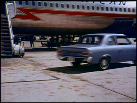 vídeos de stock, filmes e b-roll de two pretty flight attendants descend the staircase from an american airlines jet and get into their 1969 amc rambler parked just yards away on the... - 1960 1969