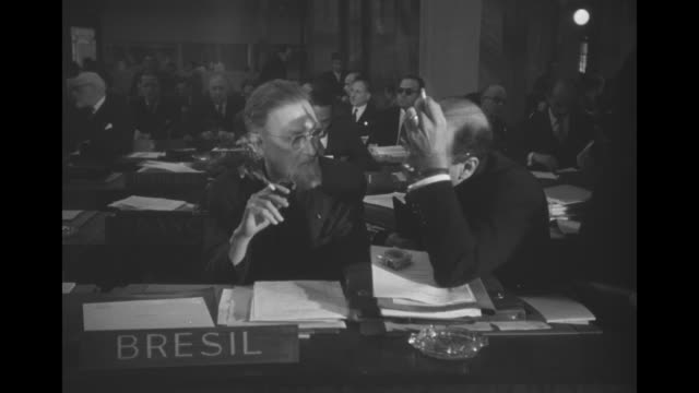 vidéos et rushes de montage unesco officials listen to proceedings at meeting / actress myrna loy listens through headphones / brazilian delegate paulo carneiro smokes a... - unesco