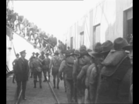 vídeos de stock e filmes b-roll de montage us marines march toward transport ship in san diego ca and walk up gangplank for transport to nicaragua / ship sails away from dock as people... - fuzileiro naval