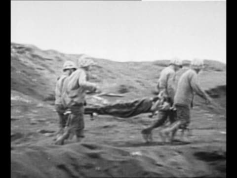 montage us medics carry wounded soldiers on stretcher/ us marines in silhouette against setting sun carry wounded comrade down hill / black / end... - battle of iwo jima stock videos & royalty-free footage