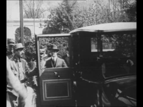 Montage US President Woodrow Wilson British Prime Minister David Lloyd George arrive in automobiles decar walk up steps of Palace of Versailles for...