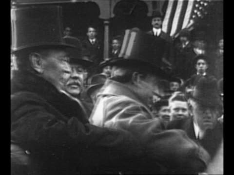 Montage US President Woodrow Wilson sits in carriage with other men / Wilson stands on corner in Milwaukee WI / Wilson stands with wife Edith /...