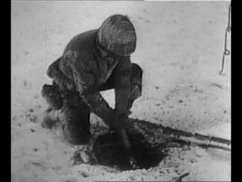 Montage US soldiers dig holes in snow and ice for posts for barbed wire fence during World War II stint in Belgium / soldier unwinds snowcovered coil...