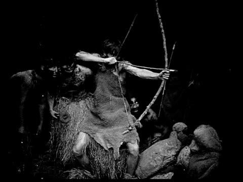 vidéos et rushes de 1914 b/w montage wide shot caveman aiming and shooting bow and arrow/ caveman standing outside cave wounded by arrow - évolution de l'espèce