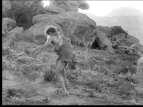 1914 B/W Montage Wide shot Caveman aiming and shooting bow and arrow outside cave/ Wounded caveman falling dead in field and other cavemen running away