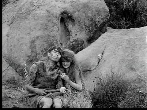 1914 B/W Montage Wide shot Caveman and cavewoman hugging on rocks near reptile and running away