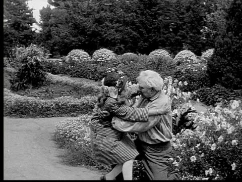 1913 b/w montage - wide shot - medium shot girl running and hugging grandfather in garden / grandfather kissing granddaughter / usa  - 1913 stock-videos und b-roll-filmmaterial