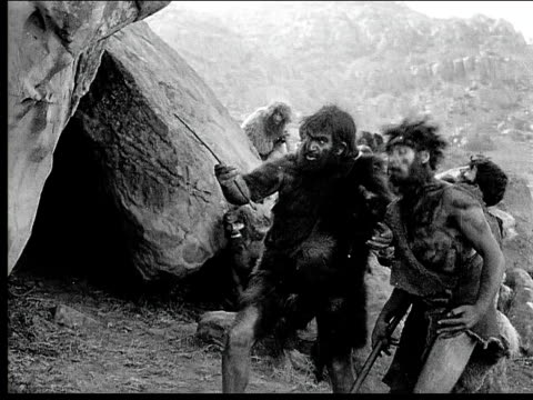 1914 b/w montage wide shot wounded caveman pulling arrow out of his torso/ caveman aiming and shooting bow and arrow/ cavemen standing outside cave wounded by arrow and falling to ground - evolution stock-videos und b-roll-filmmaterial