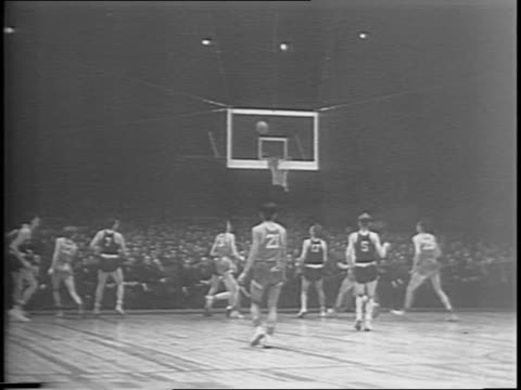 Montage wideshot of basketball court Dartmouth's Aud Brindley scores a basket crowd cheering player making a layup opposing players shaking hands at...