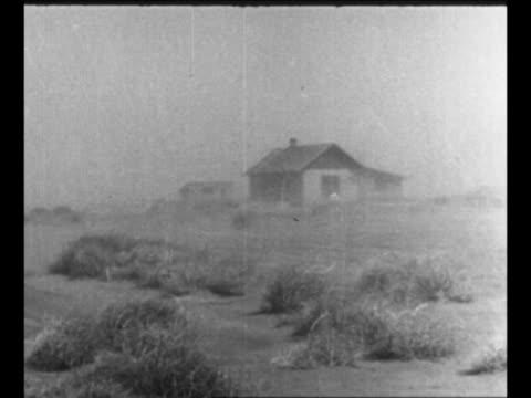vidéos et rushes de montage wind blows dust swirls tumbleweeds roll past houses buildings railroad tracks car drives past / man walks in dust storm / dust storm on farm... - la grande dépression