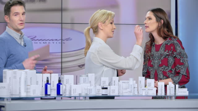 vídeos de stock e filmes b-roll de montage: woman placing some lip salve of the cosmetic line she is presenting on the female model's lips while talking to the male host of the infomercial show - anúncio de televisão