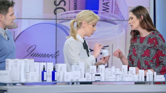 montage: woman presenting a cosmetic line on an infomercial show rubbing some cream on the female model while talking to the male host and explaining the product - television advertisement stock videos & royalty-free footage