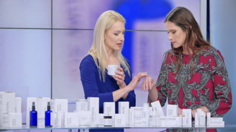montage: woman presenting a cosmetic line on an infomercial show rubbing cream onto the hand of a female model while talking to the female host - television advertisement stock videos & royalty-free footage