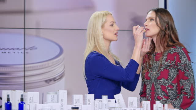 montage: woman presenting a lip salve from the cosmetic line on an infomercial show putting some on the female model's lips while talking to the female host - television host stock videos & royalty-free footage
