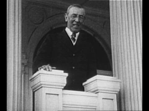 Montage Woodrow Wilson speaks smiles gets out of car walks shakes hands with man speaks to others in line of people visiting him / man hands Wilson a...