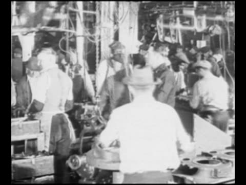 montage workers on ford motor company automobile assembly line work with car parts in factory in dearborn mi / model t car approaches camera in new... - フォード・t型モデル点の映像素材/bロール