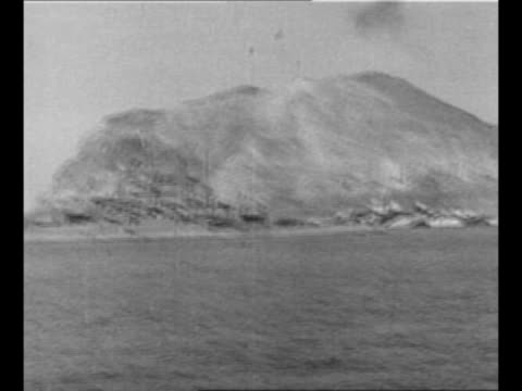 montage world war ii naval bombardment of iwo jima as battleships fire weapons / pan battleship in ocean; iwo jima in background / montage... - 空爆点の映像素材/bロール
