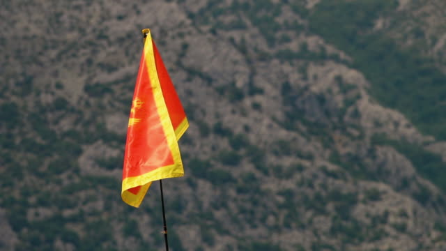 vídeos de stock, filmes e b-roll de a montenegro flag loves in the wind - moving activity