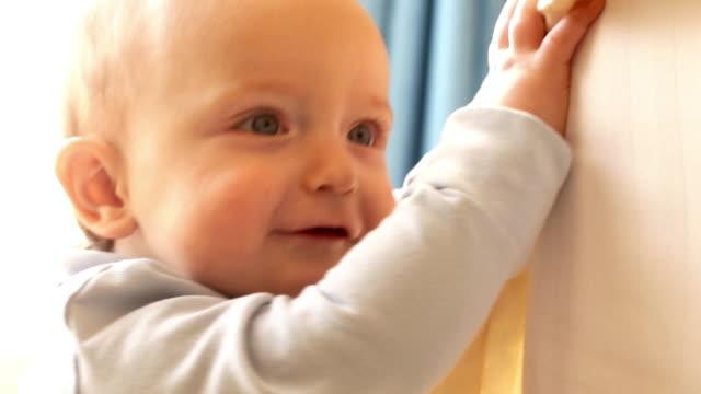 12 month old baby  playing on bed indoors. - ein männliches baby allein stock-videos und b-roll-filmmaterial