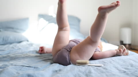 a 18 month old baby playing with a rattle and a pacifier on a bed - koncentration bildbanksvideor och videomaterial från bakom kulisserna