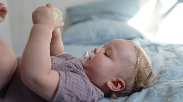 vidéos et rushes de a 18 month old baby playing with a rattle, laying on a bed - 18 23 mois