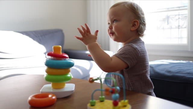 a 18 month old baby playing with colourful building kit at home - üben stock-videos und b-roll-filmmaterial